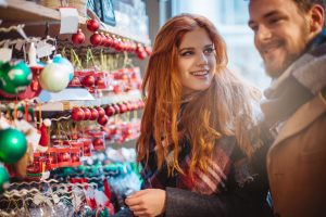 Young couple shopping at Christmas fair outdoors.