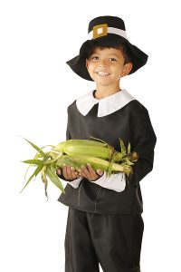 An adorable preschooler dressed as a Pilgrim happily carring an armload of fresh corn.