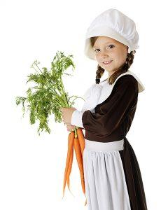 A beautiful elementary Pilgrim girl holding freshly picked carrots.