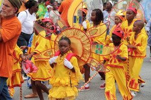 Barbados kids kadooment, a group of kids dressed in yellow costumes enjoying the carnival.