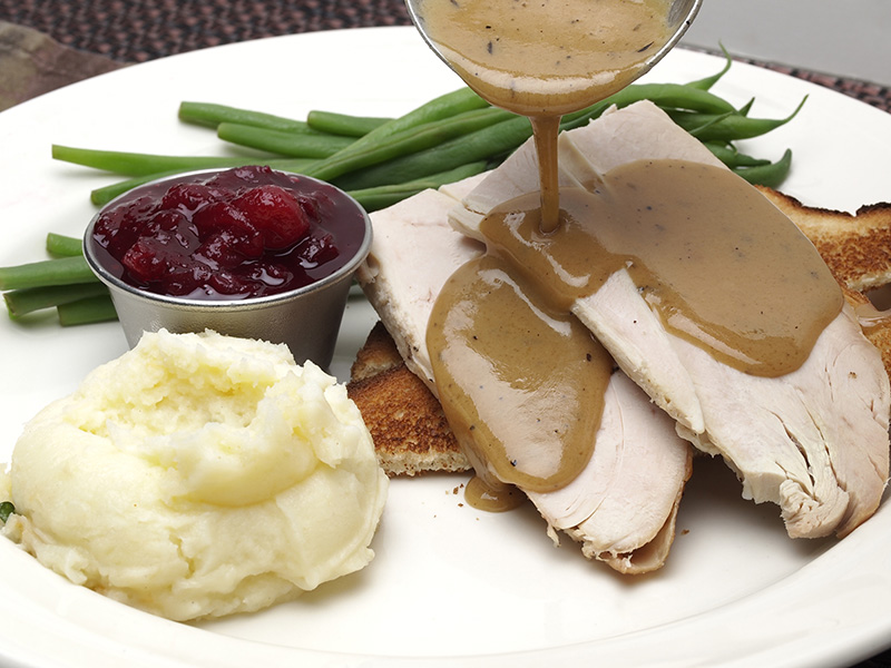 Open face turkey sandwich with green beans, cranberry sauce and mashed potatoes with gravy pouring over turkey breast meat.