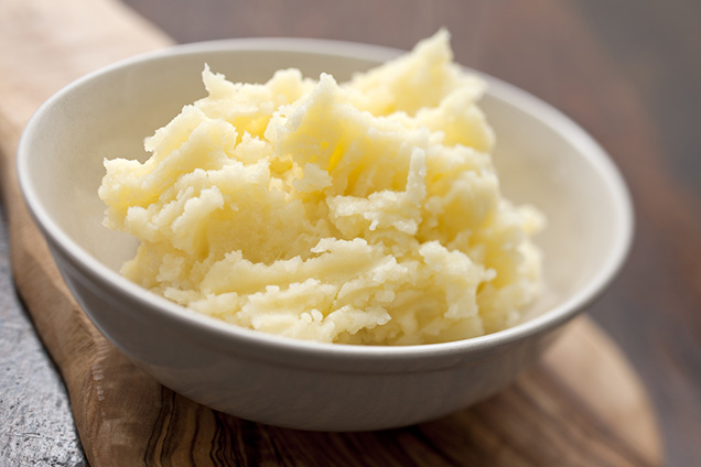 Bowl of mashed potatoes in a white bowl on a wooden surface.