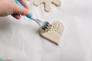 Making impressions in a salt dough heart ornament with a fork.