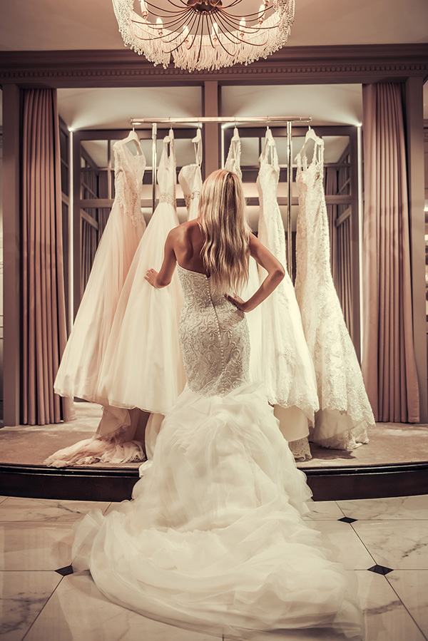 Back view of bride choosing wedding dress in modern wedding salon.