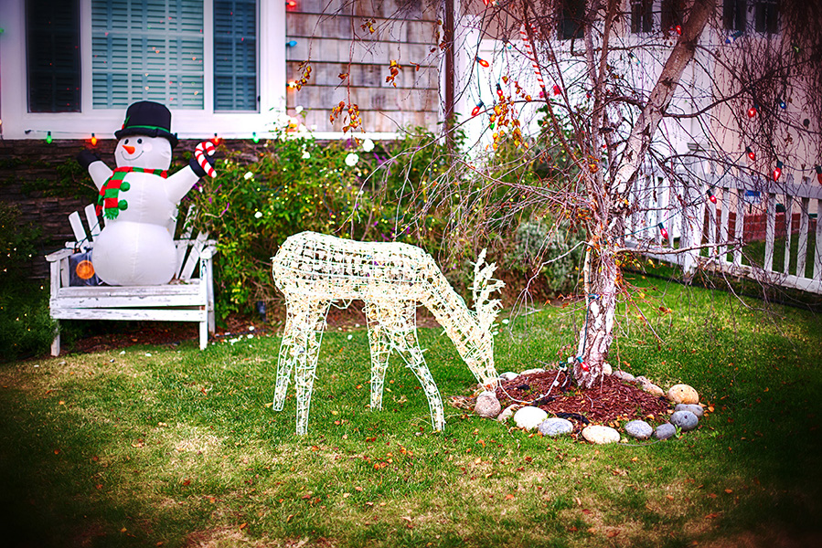 Christmas decorations in front of a house with snowman and reindeer.
