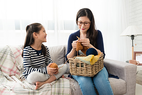 Asian kid sitting on the sofa with her mother and knitting together in the living room at home.