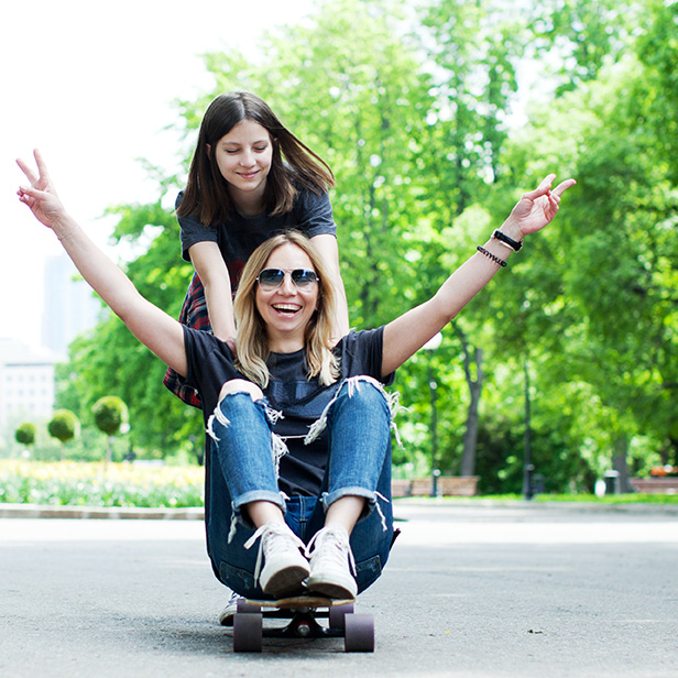 Daughter pushing her mother who is sitting on a skateboard. An example of relaxed parenting.