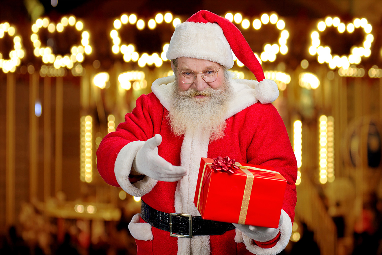 Santa Claus showing box with present standing on festive shimmering background.