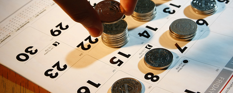 A hand stacking coins on a calendar implying saving or investing.